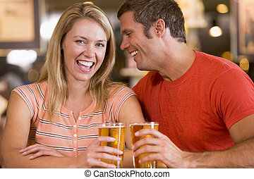 Young man in bar whispering into his girlfriends's ear