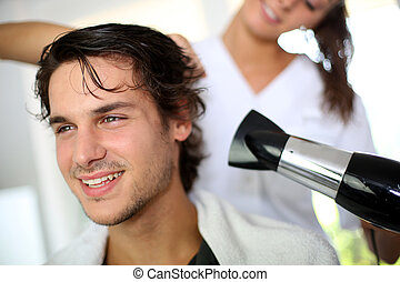 Young man in beauty salon having his hair dried