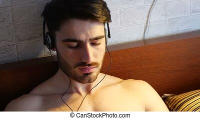 Young man in bed listening to music with headphones -...