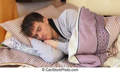 Young man in bed sleeping. Tossing and turning