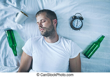 Young man in bed the morning after night out drinking