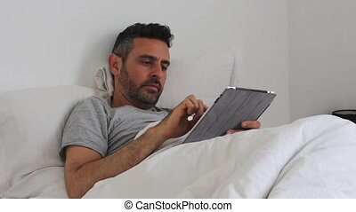 Young man in bed with smartphone and tablet