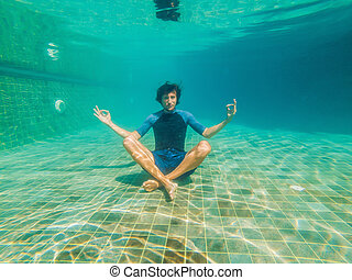 young man in black bikini in yoga position underwater in diving aquarium, full body shot, front view