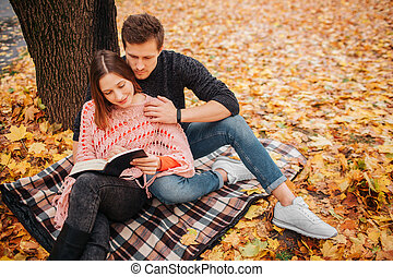 Young man in black clothes sits on blanket and look at book woman holds in hands. She read it. Young man embrace woman.