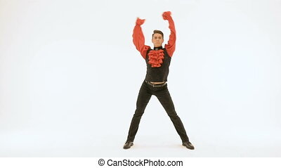 Young man in black suit and red shirt dancing on white background.