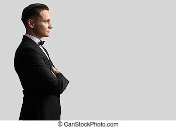 Young man in black suit looking at his side