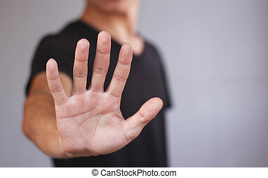 Young man in black t shirt shows his hand