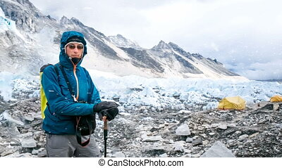 Young man in blue jacket resting after mountain climbing -...