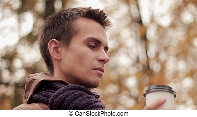 Young man in brown jacket and knitted scarf in autumn park drinks coffee out of paper cup close up