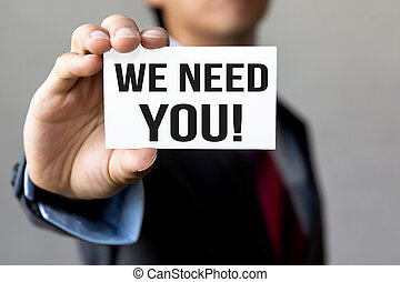 Young man in business suit shows WE NEED YOU message on white card. Business and recruitment concept