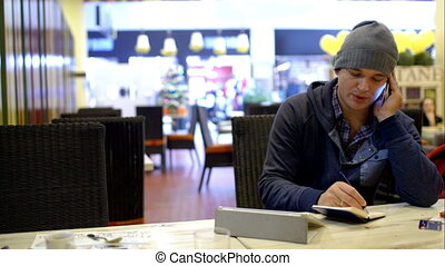 Young man in cafe making notes while talking on phone