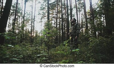 Young man in camouflage standing in the forest and looking...