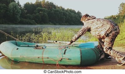 Young man in camouflage uniform puts rubber boat from the...