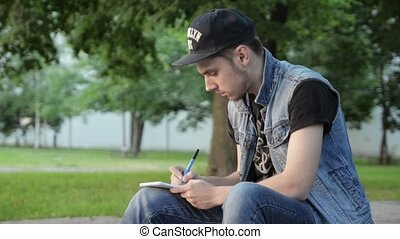 Young man in cap sit and write something on paper notebook, pulls out page.