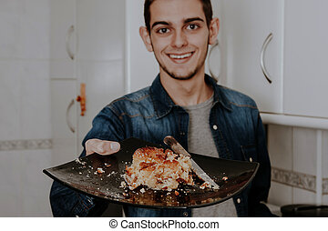 young man in casual style with the plate of cake in the apartment
