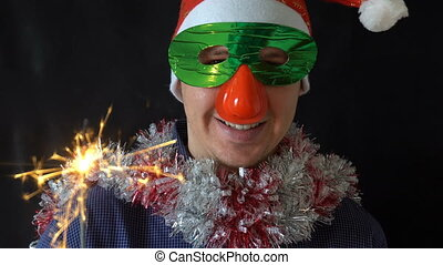 young man in Christmas hat and mask holding a burning Sparkler