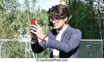 Young man in city taking photos with cell phone