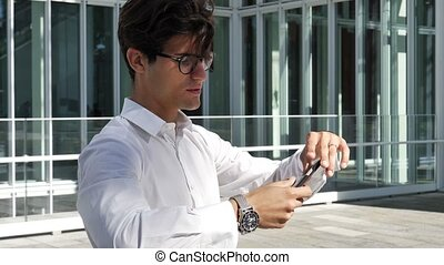 Young man in city taking selfie with cell phone