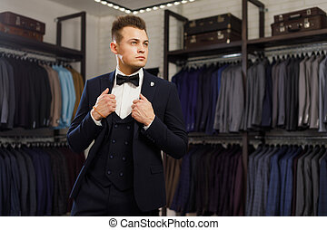 young man in classic vest against row of suits in shop