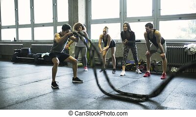 Young man in crossfit gym working out with battle rope.