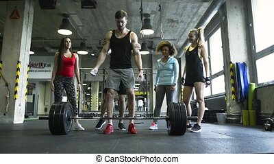 Young man in crossfit gym working out with heavy barbell.