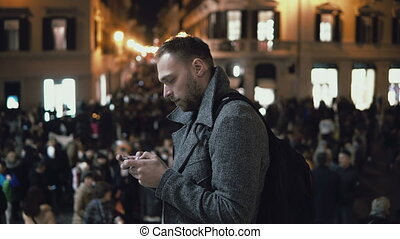 Young man in downtown in the evening. Male use the smartphone standing on the square in crowd in city centre.