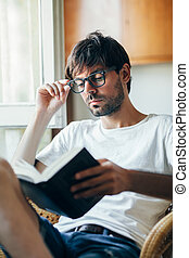 Young man in eyeglasses reading book sitting on chair