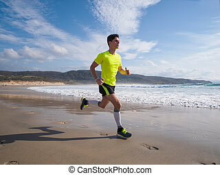 Young Man In Fitness Clothing Running Along Beach