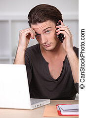 Young man in front of computer on the phone