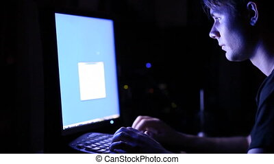Young man in front of computer screen. Dark night room.