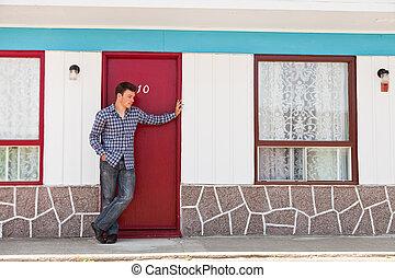 Young man in front of red door