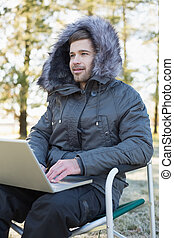 Young man in fur hood jacket using laptop in the forest on a...