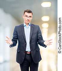 Young man in glasses and suit in office posing in studio