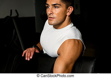 young man in gym exercising with dumbbells