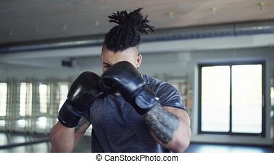 Young man in gym with boxing gloves doing exercise indoors.