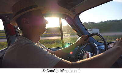 Young man in hat holding hands on a steering wheel and driving a retro car with sun flare at background. Caucasian guy traveling in a vintage vehicle at countryside. Side view Slow motion Close up