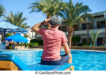 Young man in hat sitting on a sun lounger near swimming pool, concept time to travel. Relax in the pool summer in Egypt