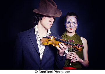 young man in hat with violin and young woman in veil with bouquet of roses on black background