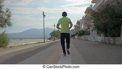 Young man in headphones runs on road of city Perea, Greece