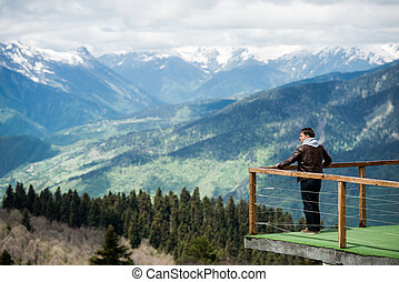Young man in hood looking on the mountain landscape from wooden pier at morning. Rear view photo