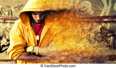 Young man in hooded sweatshirt on grunge wall. Particles...