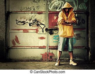 Young man portrait in hooded sweatshirt / jumper on grunge graffiti wall
