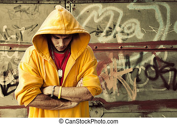 Young man in hooded sweatshirt on grunge wall