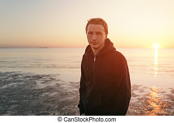 Young man in hoodie portrait on sea coast in sunset