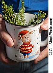 young man in jeans and an office shirt holding a Christmas mug with a symbol of the year pig and Christmas tree. Layout for design of winter gifts.