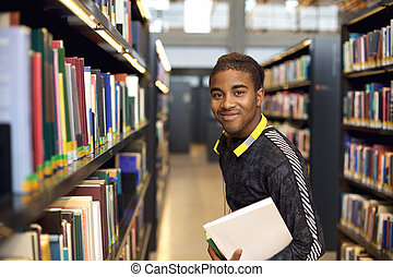 Young man in library for reference books