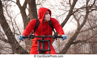 Young man in medical mask and gloves coughing in countryside...