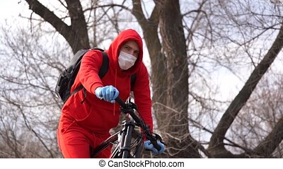Young man in medical mask and gloves sitting on bicycle in ...