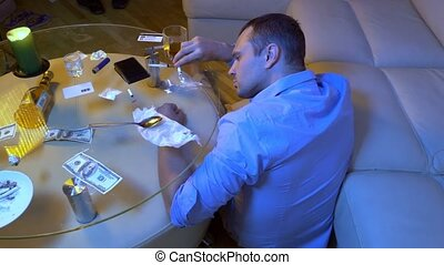 young man in office shirt prepares a line from drugs to sniff while sitting on a sofa in the living room.