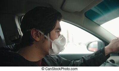 Young man in protective mask driving a car